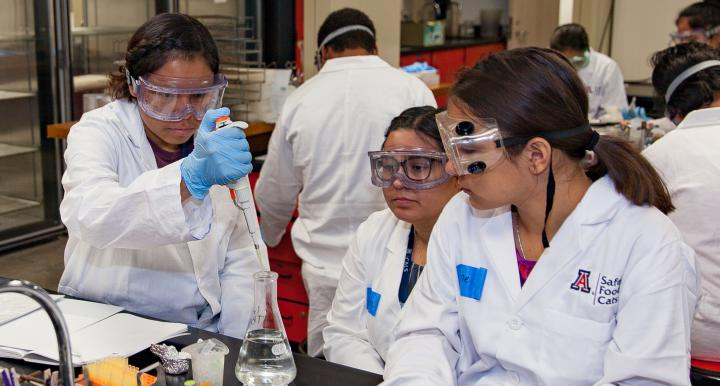 two female students with female instructor in lab